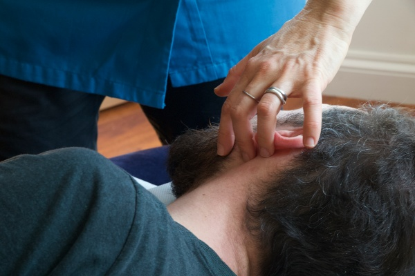 Chiropractic adjustment to client's ear.