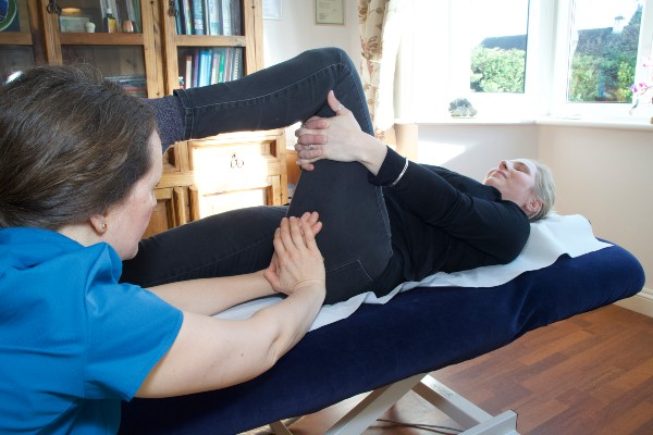 Chiropractor places leg on client's thigh to perform an adjustment.