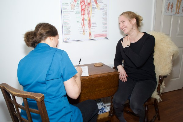 Chiropractor takes client's history during first session.